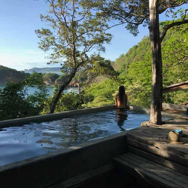 Woman in infinity pool overlooking view